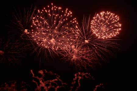 Holiday Fireworks with bright flashes and sparks of different colors in the night sky