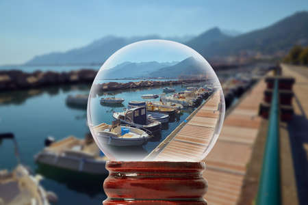 Small dock in Italy for boats and yachts with mountains on the background through a glass transparent ball