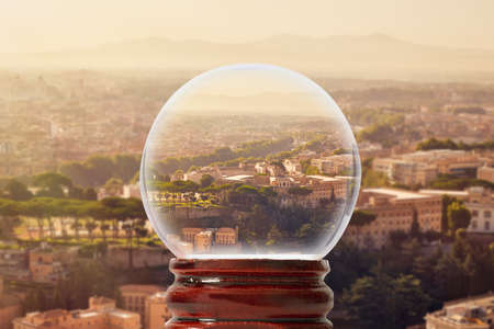 Panorama of Rome on a summer sunny morning with mountains in the background through a glass transparent ball