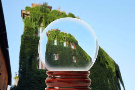 The building is completely overgrown with vine lightly illuminated by the rays of the rising sun, Trastevere district, through a glass transparent ball Rome, Italy