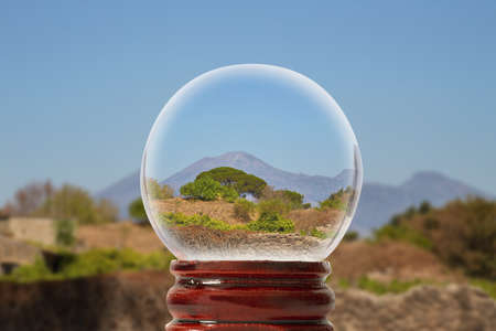 Pompeian landscape on a summer sunny day with Vesuvius in the background through a glass transparent ball Stock Photo