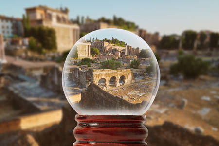 View of the ruins of the Roman Forum without people lit by the evening sun in a glass transparent bowl