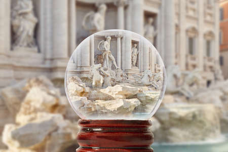 One of the most significant sights of Rome - the Trevi Fountain on a bright summer day without people through a glass transparent ball