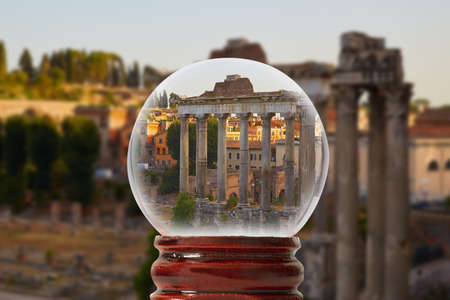 Roman forum. Columns of the temple of Saturn in the evening. Rome, Italy through a glass transparent ball Stock Photo