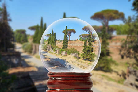 The road between ruins in Pompeii on a summer sunny day through a glass transparent ball