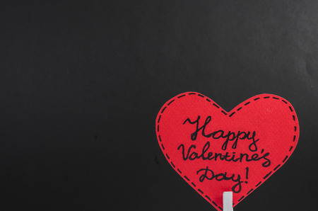 Red heart on the clothespin with the greeting happy Valentines day on dark background Stock Photo