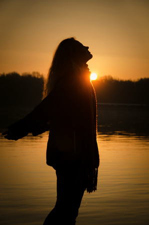 placidity: girl silhouette at sunrise Stock Photo