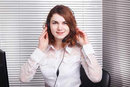 garniture: Portrait of happy smiling cheerful young support phone operator in headset
