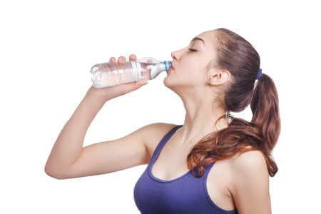 Beautiful athletic girl looks drinks water from a bottle photo