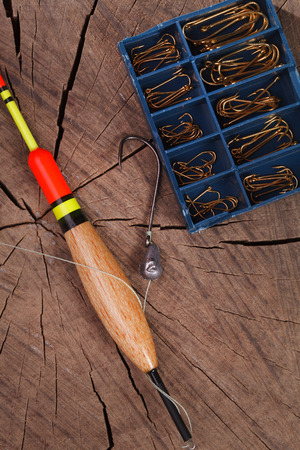 bobber: Fishing tools hook and bobber on a wooden background