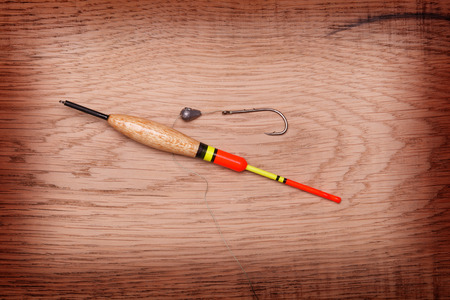 fishing bobber: Fishing tools hook and bobber on a wooden background