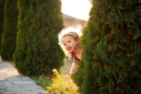 Het gelukkige meisje kijkt uit de struik Stockfoto
