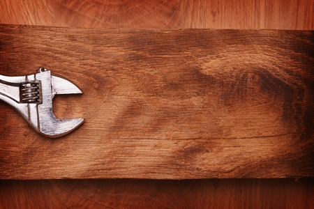 Adjustable wrench on wooden background