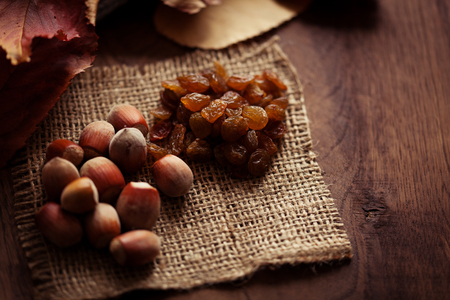 autumn food: Hazelnuts and raisins with autumn leaves on the background of a wooden table Stock Photo