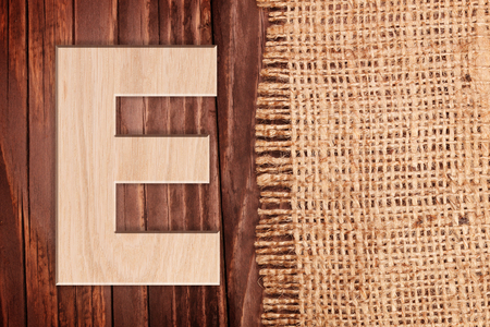 e pretty: Wooden alphabet letter symbol - E. On wooden table background with burlap