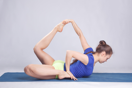 practicing: Woman practicing advanced yoga