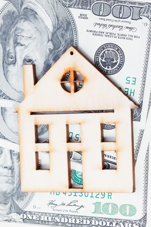 building loan: Model of wooden house with dollar bills. House building, loan, real estate, cost of housing or buying a new home concept.