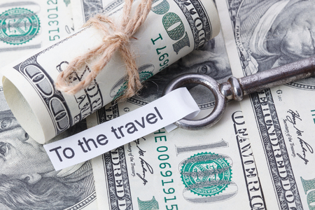 key fob: Money and business idea, The dollar bills tied with a rope, with a sign on key fob- To the Travel