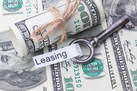 key fob: Money and business idea, The dollar bills tied with a rope, with a sign on key fob - Leasing Stock Photo