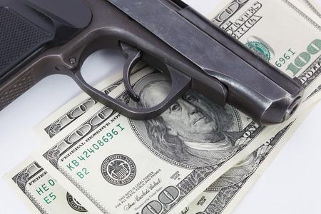 extortion: Black gun is lying on dollar bills