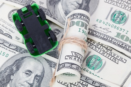 pkw: Car stands on dollar banknotes. cost of buying a car, fuel, insurance and other car costs