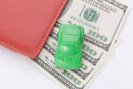 fcc: Car stands on dollar banknotes. cost of buying a car, fuel, insurance and other car costs