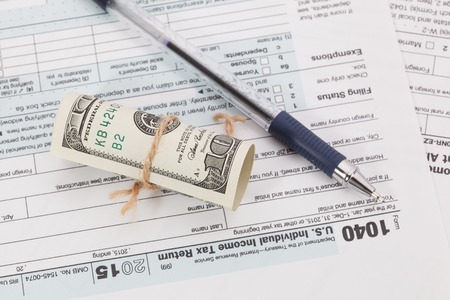 taxpayer: Money and pen on tax form background