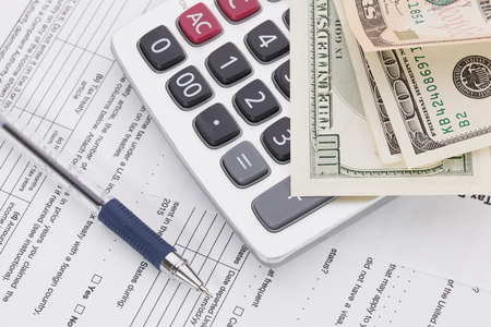 taxpayer: Money and pen with calculator on tax form background Stock Photo