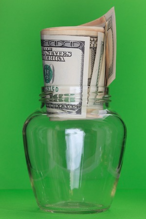 meanness: Money in glass jars, on Green background Stock Photo