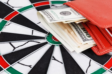 one hundred dollar bill: Close up view of red arrow and one hundred dollar bill on dart board.