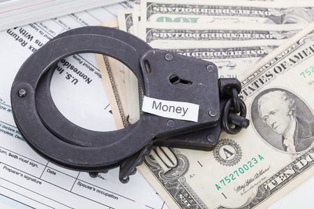 imprison: Handcuffs and money with sign - money on tax form background