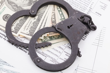 many dollar bills with handcuffs, on tax form background