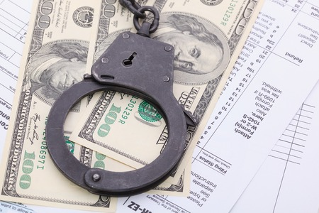 drug bust: many dollar bills with handcuffs, on tax form background