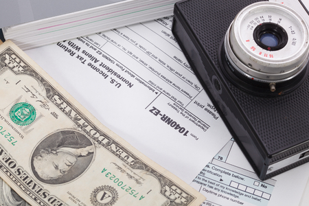 tax form: Money and camera on tax form background