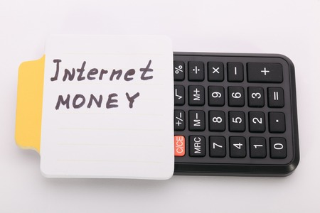 motivator: Concept write - Internet Money. Sign lays on calculator