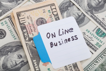 motivator: Concept write - On Line Business. Sign lays on money background Stock Photo