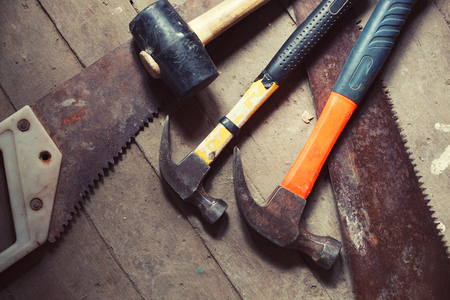 lays: A variety of hammers and saws lays on wooden floor