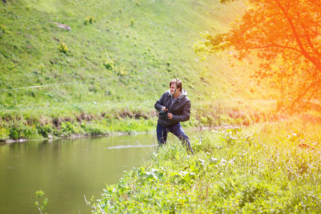 hand line fishing: Fishing with a fishing rod on the river