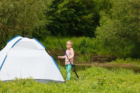 hand line fishing: Cute small boy fishing on the river. Camping on the bank of river