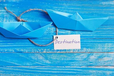 sailingboat: Paper Boat with a sign Destination - travel concept