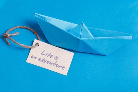 Paper Boat with a sign Life is adventure- travel concept