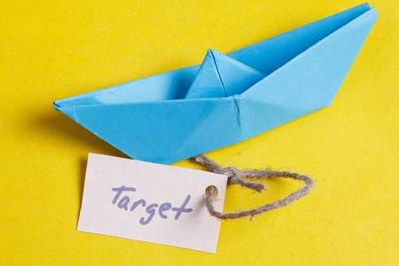 sailingboat: Paper Boat with a sign Target - travel concept