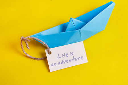 sailingboat: Paper Boat with a sign Life is adventure- travel concept