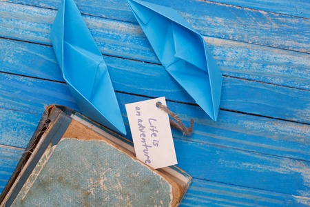 sailingboat: Paper Boat with vintage book and sign Life is an adventure - travel concept