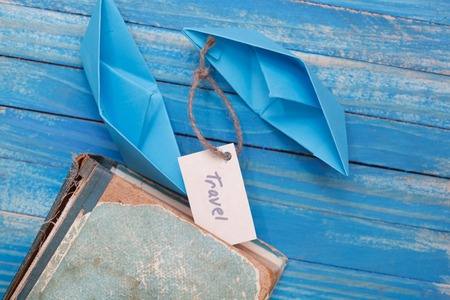 Paper Boat with a sign Travel with vintage book - travel concept Stock Photo