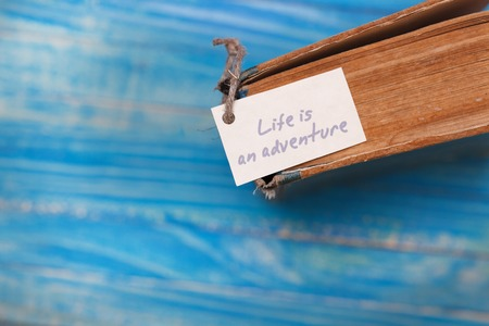 Life is adventure sign on old book - vintage style