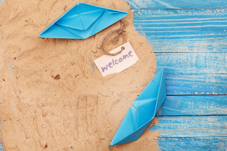sailingboat: Paper Boat with shells and sand with sign - Welcome. Vocation and travel background