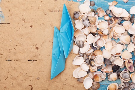 vocation: Paper Boat with shells and sand. Vocation and travel background