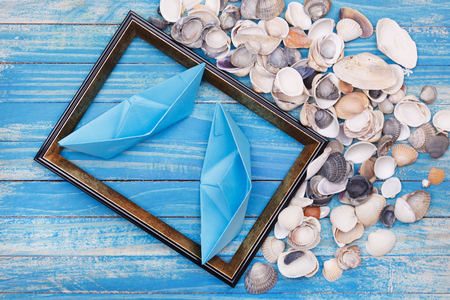 Blue paper boats and Sea shells in photo frame