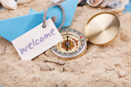 Compass in the sand with Message - Welcome